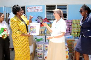 Mrs. Jean Kapata, President of ZAM presents donation to Sr. Kay O'Neil, administrator of Little Assisi