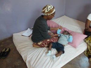Sister Mambwe (Physiotherapist) attending to a child in Little Assisi